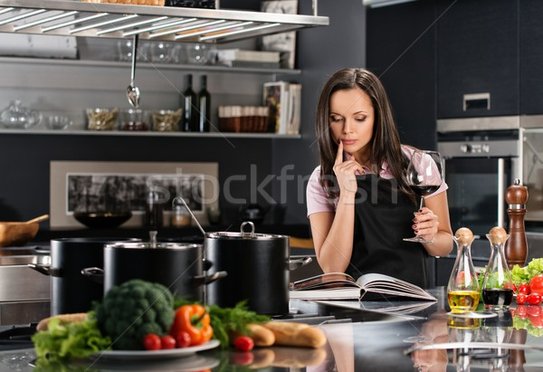 Cheerful young woman in apron on modern kitchen with cookbook and glass of wine  Stock photo © Nejron