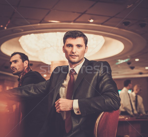 Two fashionable men in suits behind table in a casino Stock photo © Nejron