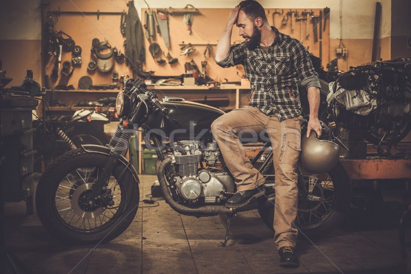 Rider and his vintage style cafe-racer motorcycle in customs garage  Stock photo © Nejron