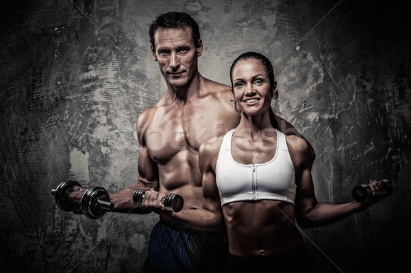 Athletic man and woman with a dumbbells Stock photo © Nejron