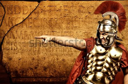 Stock photo: Roman legionary soldier in front of  wall with ancient writing