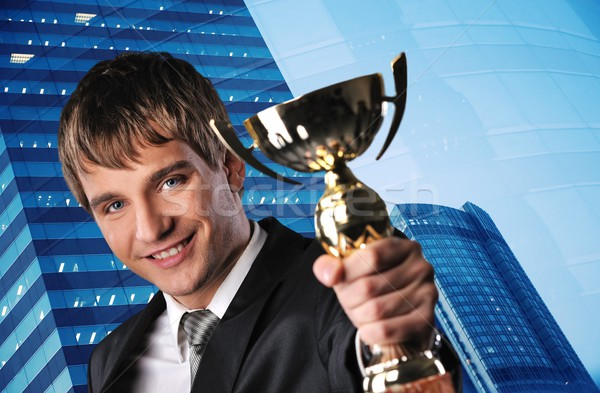 Happy businessman with a golden cup against his office building Stock photo © Nejron