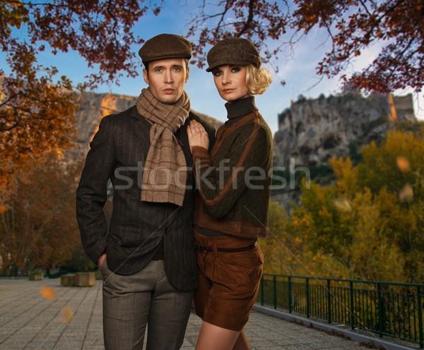 Elegant couple in caps against autumnal landscape Stock photo © Nejron
