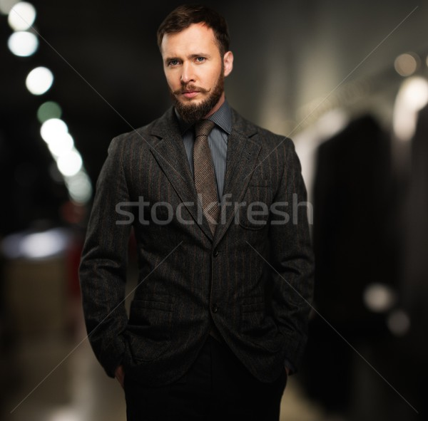 Handsome well-dressed man with beard in a clothing store Stock photo © Nejron