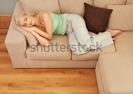 Happy young woman lying on a sofa with TV remote Stock photo © Nejron