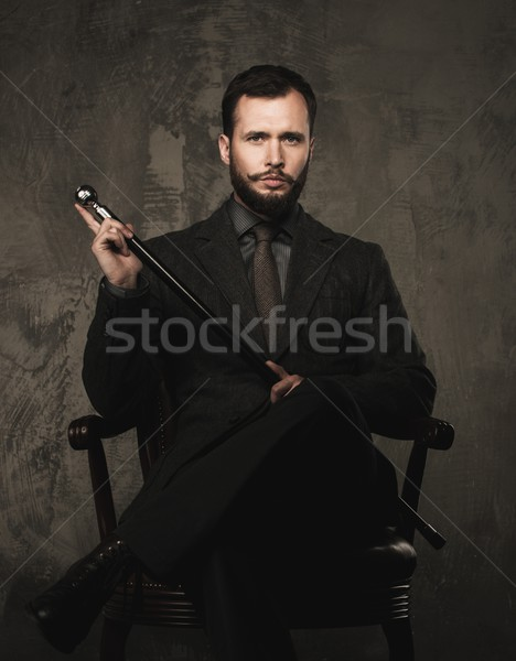 Handsome well-dressed with stick sitting in leather chair  Stock photo © Nejron