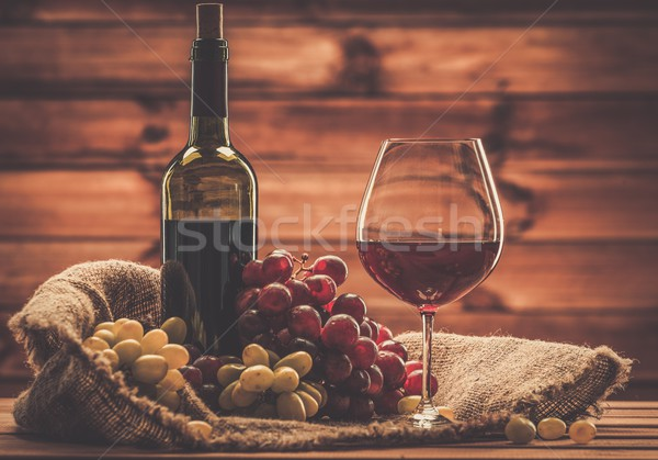 Bottle of red wine, glass and grape in basket in wooden interior  Stock photo © Nejron