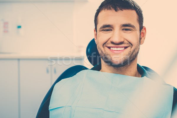 Smiling young man at dentist's surgery Stock photo © Nejron