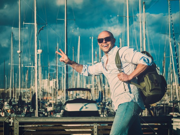 Happy middle-aged man with backpack against yacht port Stock photo © Nejron