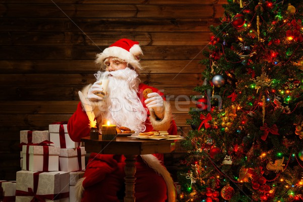 Santa Claus  in wooden home interior with glass of milk and oatmeal cookies Stock photo © Nejron
