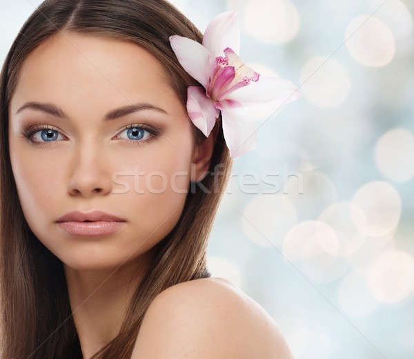 Beautiful young girl with lily flower in her hair over blurred background  Stock photo © Nejron