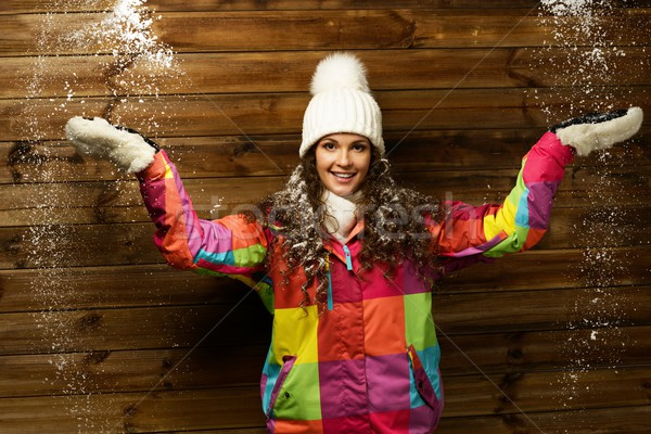 Smiling woman in ski jacket and white hat standing against wooden house wall under snow  Stock photo © Nejron