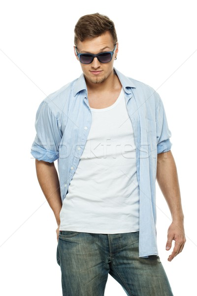 Stylish man in blue shirt and jeans wearing sunglasses isolated on white Stock photo © Nejron
