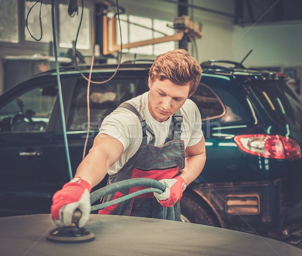 Serviceman performing grinding with machine on a car bonnet in a workshop Stock photo © Nejron