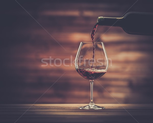 Pouring red wine into the glass against wooden background Stock photo © Nejron