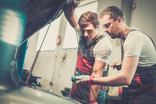 Two mechanics checking oil level in a car workshop Stock photo © Nejron