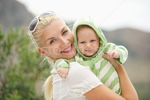 Stock photo: Mother with her adorable baby outdoors