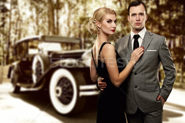 Stock photo: Retro couple against old car.