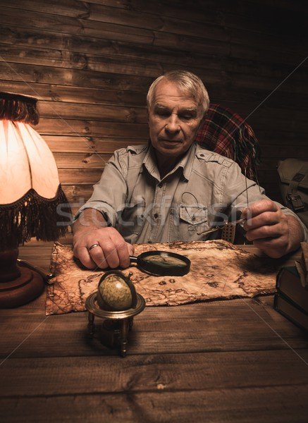 Senior man with magnifier looking at vintage map in homely wooden interior  Stock photo © Nejron