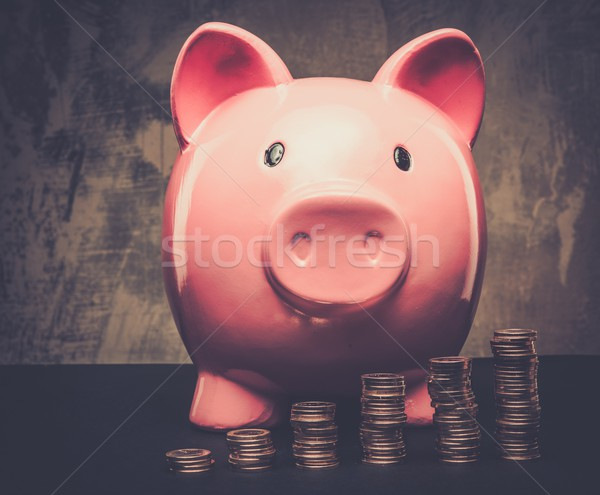 Piles of coins in front of piggybank Stock photo © Nejron