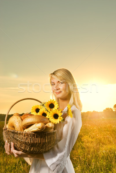 Beautiful young woman with a basket full of fresh baked bread Stock photo © Nejron