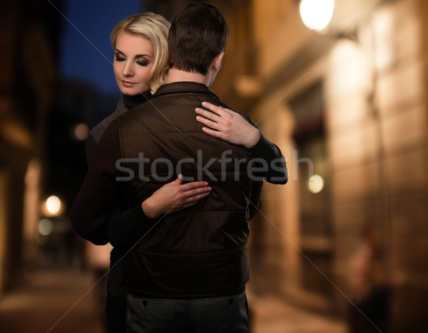 Blond woman embracing man in brown vest outdoors at night Stock photo © Nejron