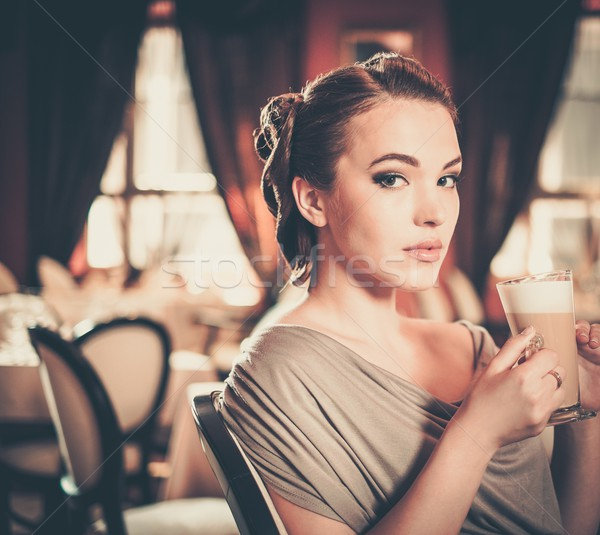 Beautiful young girl with cup of coffee alone in a restaurant Stock photo © Nejron