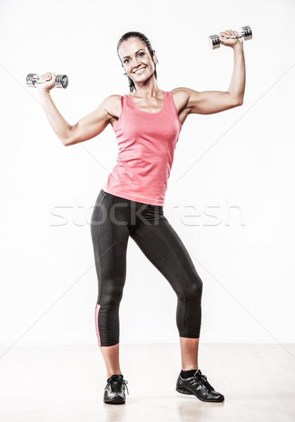 Beautiful woman doing fitness exercise with dumbbells Stock photo © Nejron