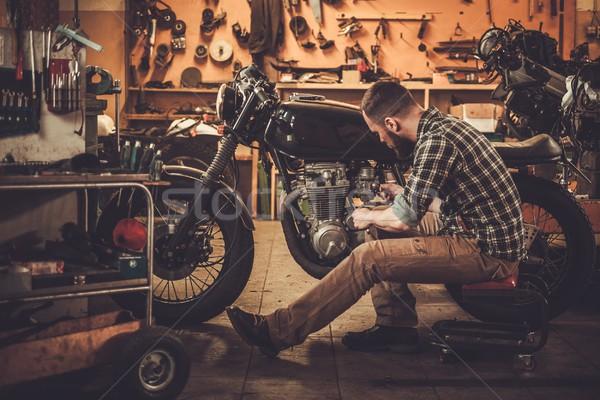 Mechanic building vintage style cafe-racer motorcycle  in custom garage Stock photo © Nejron