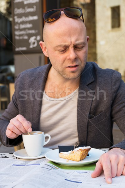 Middle-aged man reading newspaper behind table in street cafe during coffee pause Stock photo © Nejron