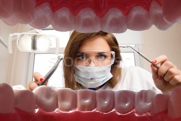 View at young female dentist with dental tools from patient's mouth  Stock photo © Nejron