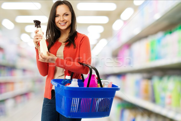 Beautiful cheerful brunette woman with basket full and bottle of cleanser in a shop Stock photo © Nejron