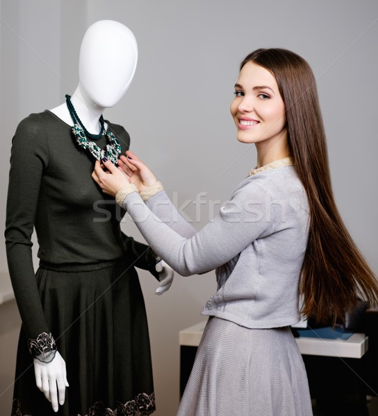 Young woman looking at necklace on mannequin in showroom Stock photo © Nejron