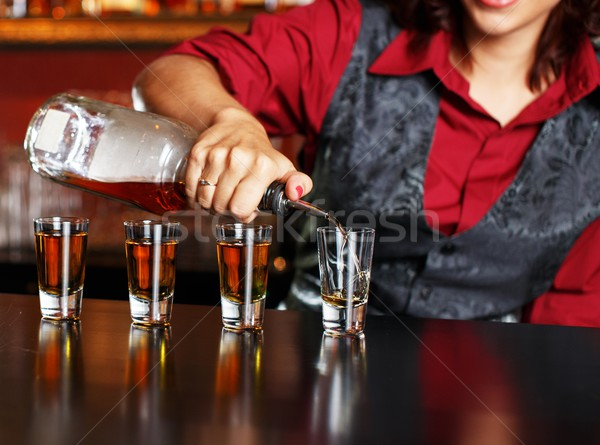 Beautiful redhead barmaid making shots Stock photo © Nejron