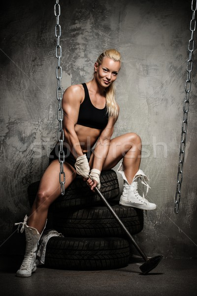 Beautiful muscular bodybuilder woman sitting on tyres and holding hammer Stock photo © Nejron