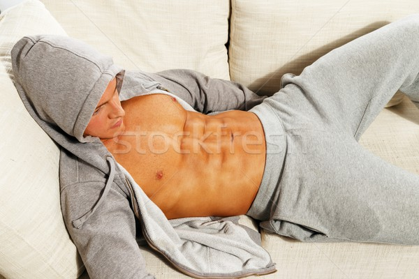 Sporty man in grey hoodie with muscular torso relaxing on sofa Stock photo © Nejron