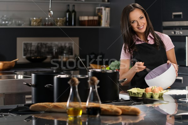 Young woman in apron whisking eggs for a dough on a modern kitchen Stock photo © Nejron