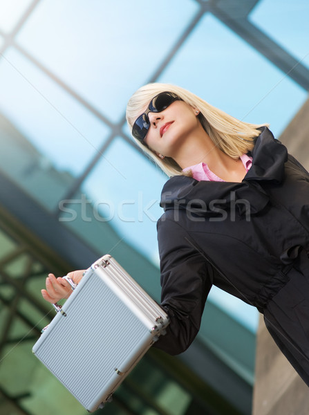 Beautiful young woman with silver case near the modern office bu Stock photo © Nejron