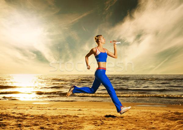 Beautiful young woman running on a beach at sunset Stock photo © Nejron