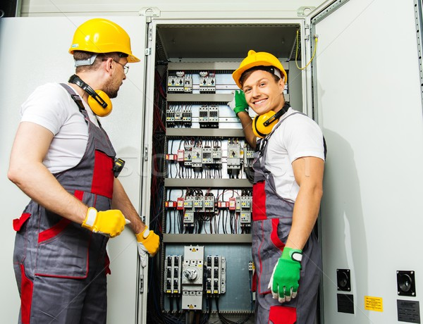 Two electricians in a safety hat and headphones on a factory Stock photo © Nejron