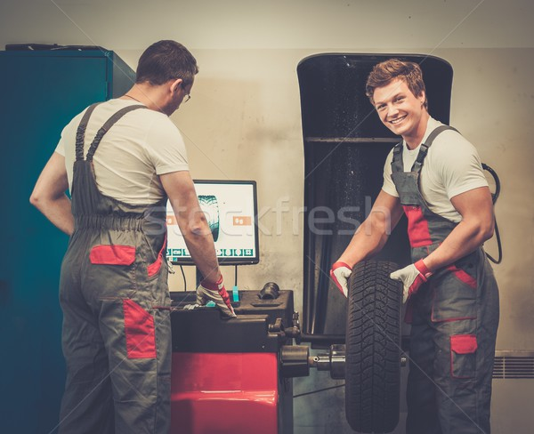 Two mechanics balancing wheel in a car workshop Stock photo © Nejron