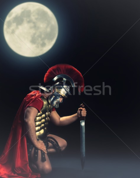 Legionary soldier standing on a knee at night time Stock photo © Nejron