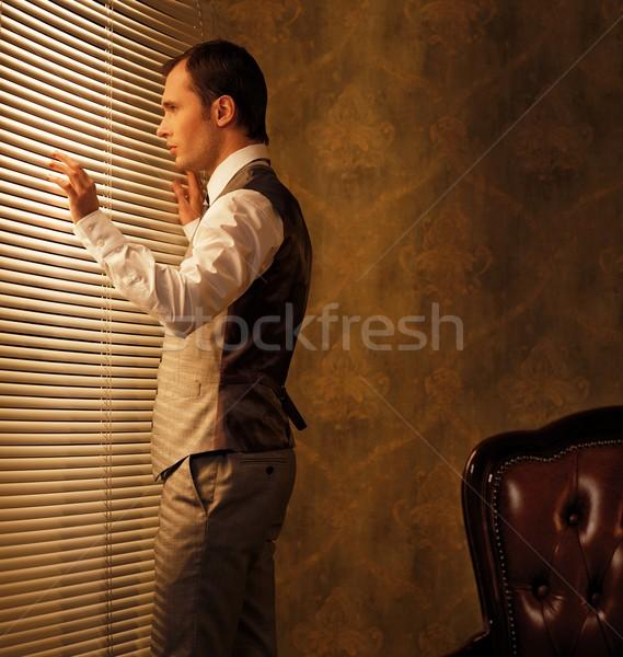 Man looking through jalousie Stock photo © Nejron