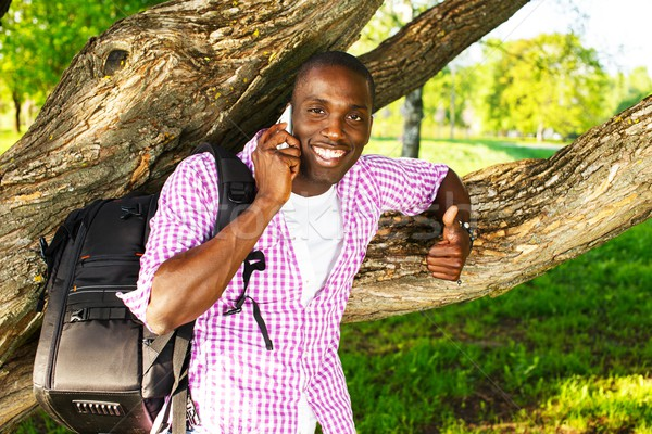 Young smiling african american man with rucksack in a park talking over mobile phone Stock photo © Nejron