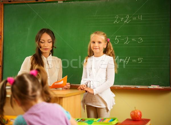 Little schoolgirl answering near blackboard in school Stock photo © Nejron