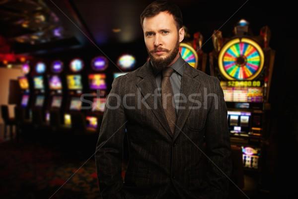 Jóképű férfi rés gépek kaszinó pénz Stock fotó © Nejron