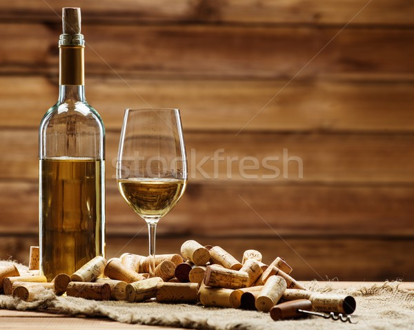 Bottle and glass of white wine on a wooden table among corks  Stock photo © Nejron