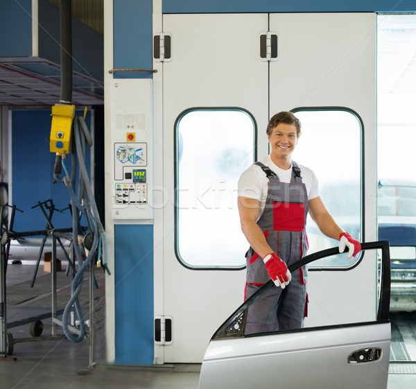 Cheerful serviceman with car door near paint booth in a car body workshop Stock photo © Nejron
