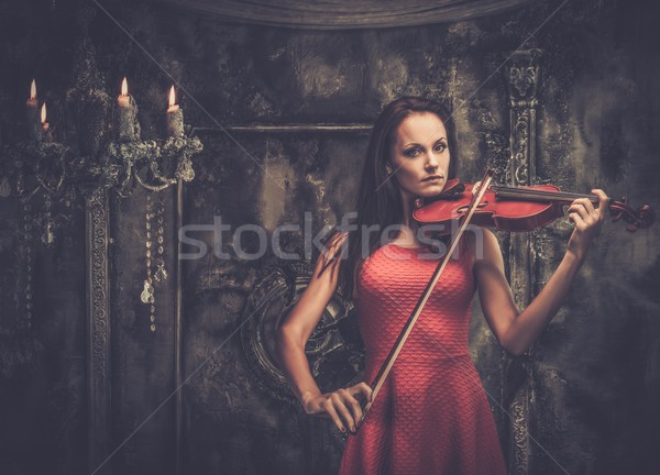 Young woman in red dress playing violin in mystic interior  Stock photo © Nejron