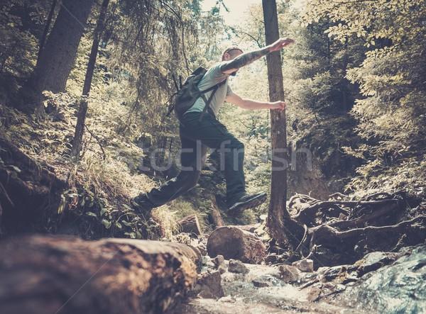 Uomo escursionista jumping stream montagna foresta Foto d'archivio © Nejron